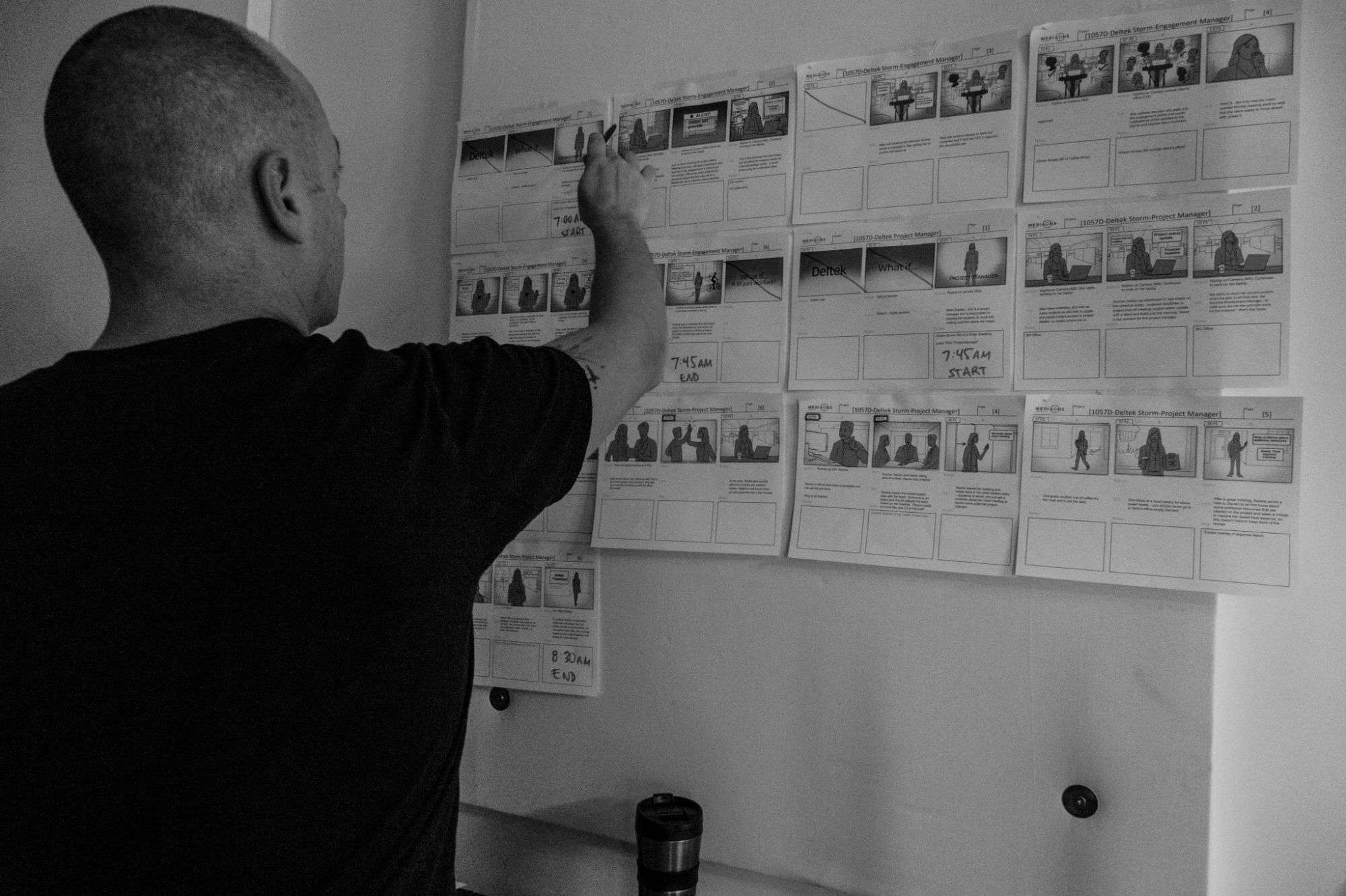 Producer of Media One Creative reviewing video storyboard - Black and White image